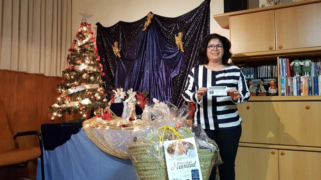 Ganadora del sorteo de la cesta de navidad del 2020 junto al nacimietno de la congregación.