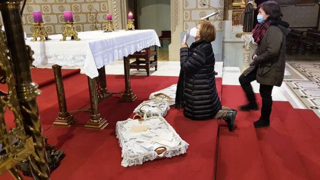 Josefina rezando ante el altar del santuario y las cartas que San José ha recibido.