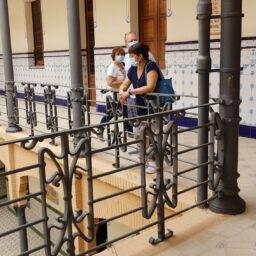 visita guiada en el claustro del santuario. Tres personas admiran la belleza del edificio